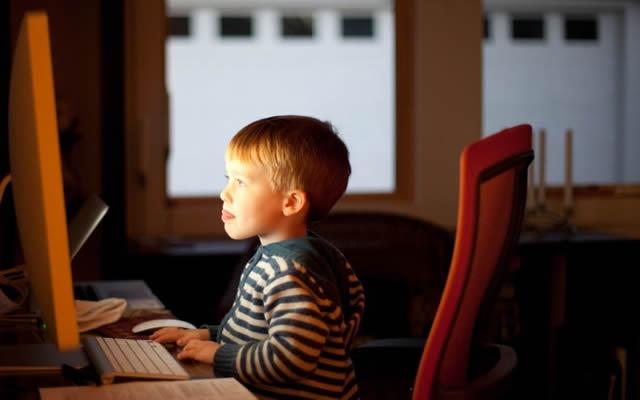 Ребенок увлечено смотрит в монитор компьютера